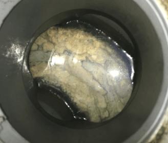 京都府伏見区の汚水マスの中に油脂や食べかす、洗剤などが層になって固まったものが詰まっている様子